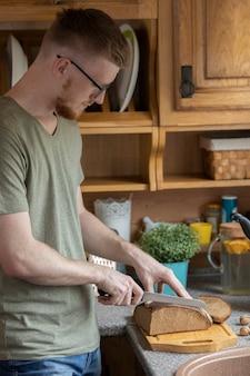Uomo barbuto che taglia il pane di segale sul bordo di legno con il coltello sulla cucina di stile rustico