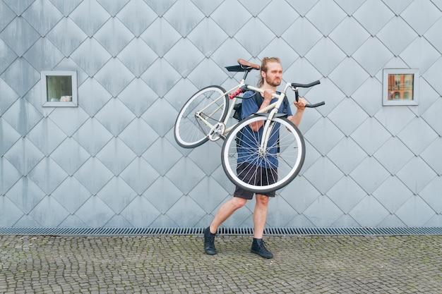Uomo barbuto che trasporta la sua bicicletta all'aperto