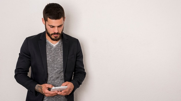 Uomo barbuto che utilizza smartphone su fondo bianco