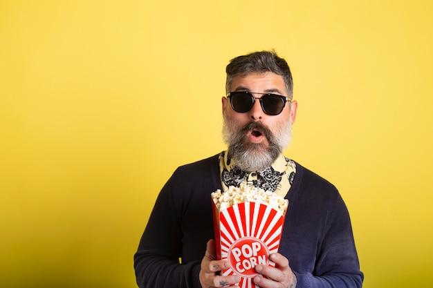 Uomo barbuto con gli occhiali da sole che mangia popcorn stupito guardando un film su sfondo giallo.