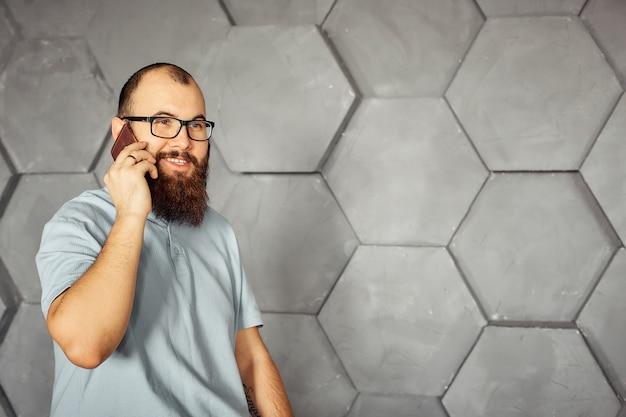 Uomo barbuto con gli occhiali parlando su un telefono cellulare.