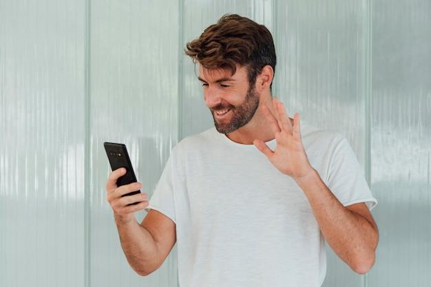 Uomo barbuto con il telefono che rinuncia alla macchina fotografica