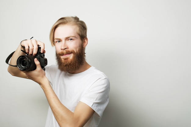 Uomo barbuto con una fotocamera digitale