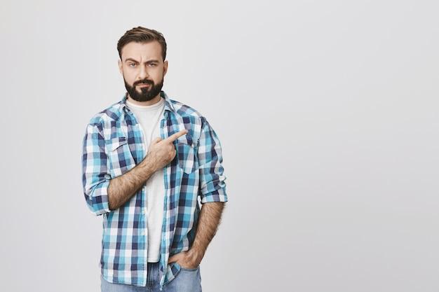 Uomo barbuto dall'aspetto serio scettico che indica l'angolo superiore destro