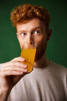 Uomo barbuto del readhead riccio che beve il succo di arancia