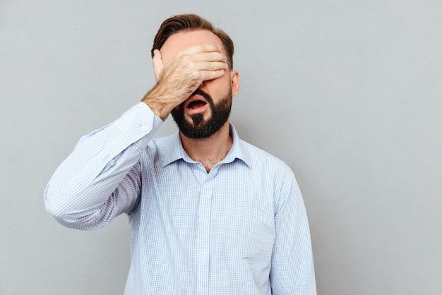 Uomo barbuto dispiaciuto in vestiti di affari che la coprono gli occhi