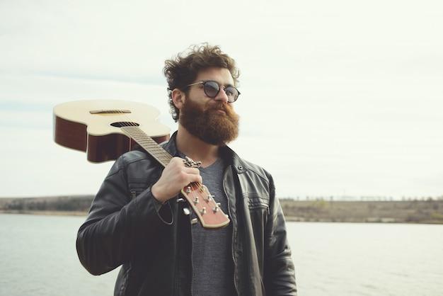Uomo barbuto e chitarra, vicino al fiume