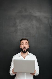 Uomo barbuto emozionante che tiene personal computer d'argento e che guarda sulla macchina fotografica, isolata sopra grigio scuro