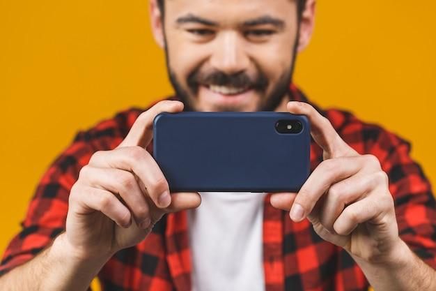 Uomo barbuto emozionante in camicia di plaid che gioca sullo smartphone isolato sopra la parete gialla.
