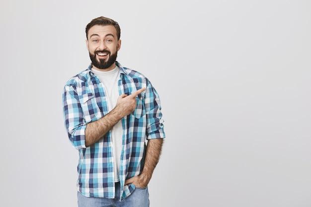 Uomo barbuto entusiasta che punta il dito a destra