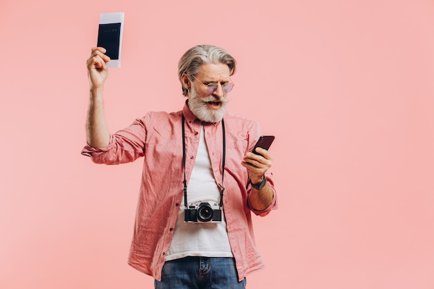 Uomo barbuto felice in occhiali da sole che tengono un telefono cellulare e un passaporto con i biglietti sul rosa