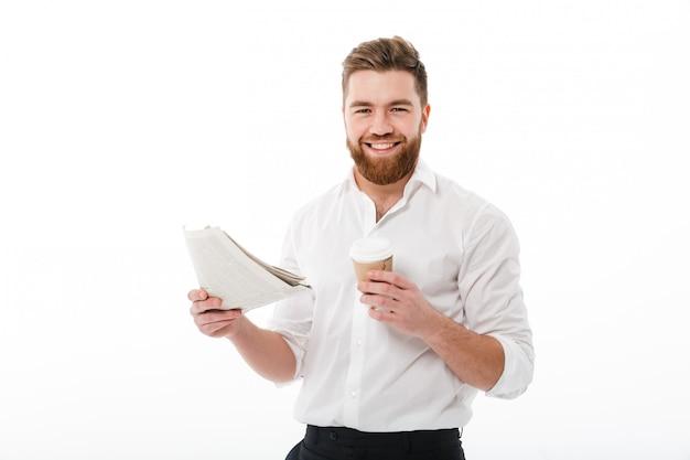 Uomo barbuto felice in vestiti di affari che tengono giornale