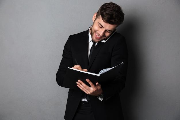 Uomo barbuto felice in vestito nero che prende le note mentre parlando sullo smartphone