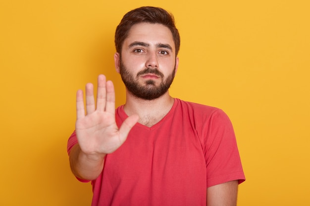 Uomo barbuto giovane che indossa la maglietta casuale rossa che sta con la mano di gesto di avvertimento di arresto e che esamina macchina fotografica con il fronte serio