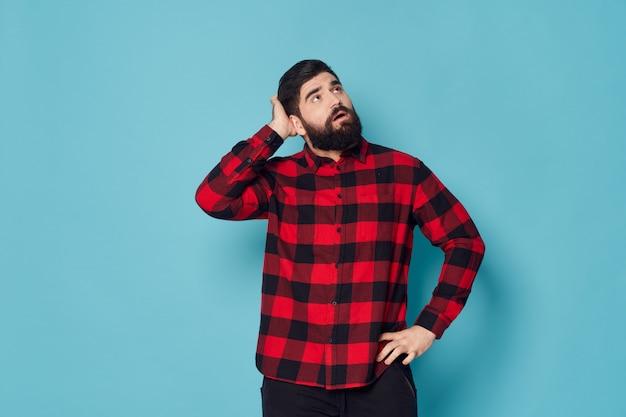 Uomo barbuto hipster con camicia a quadri in posa perplesso