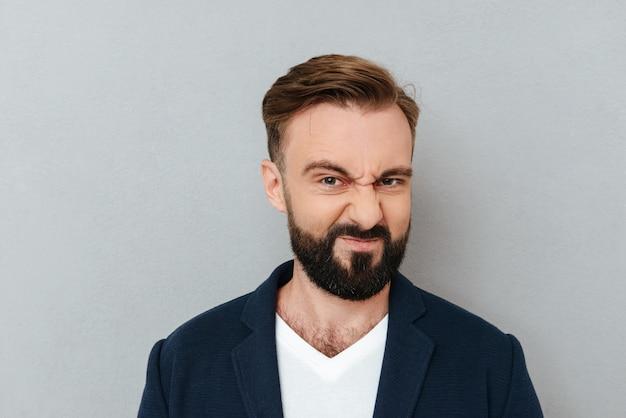 Uomo barbuto in affari disgustati vestiti e guardando la telecamera su grigio
