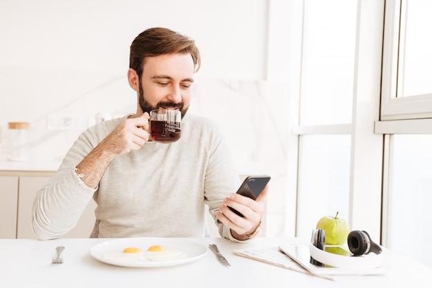 Uomo barbuto in camicia casual, bere il tè e l'utilizzo di smart phone, pur avendo un pasto sano con friggere le uova a casa