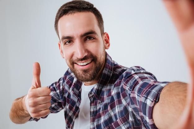 Uomo barbuto in camicia che fa selfie e che mostra pollice su