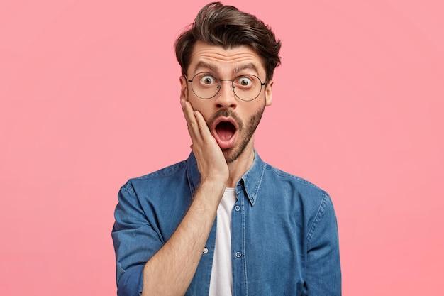 Uomo barbuto in camicia di jeans e occhiali rotondi