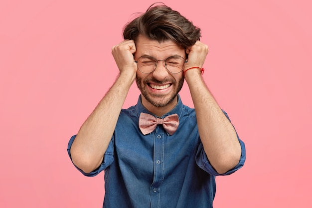Uomo barbuto in camicia di jeans e papillon rosa