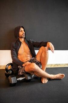 Uomo barbuto in felpa con cappuccio a riposo dopo un allenamento