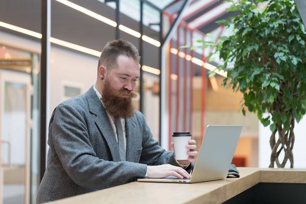 Uomo barbuto in giacca di lana che lavora su un computer portatile nella caffetteria