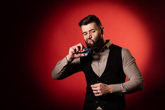 Uomo barbuto in maglia su fondo rosso. gli uomini si tagliano la barba con le forbici da parrucchiere