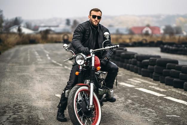 Uomo barbuto in occhiali da sole e giacca di pelle seduto su una moto sulla strada.