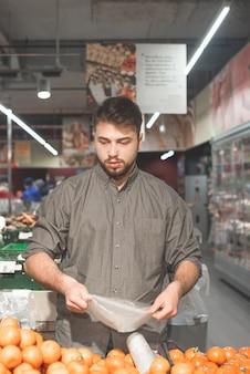 Uomo barbuto in piedi nel supermercato nella sezione frutta e fare shopping.