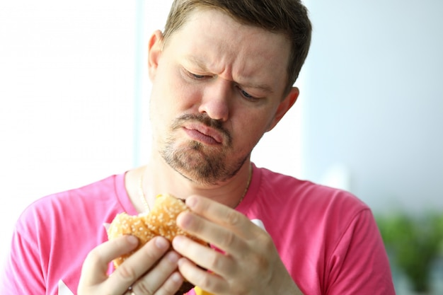 Uomo barbuto infelice che esamina hamburger con sospetto