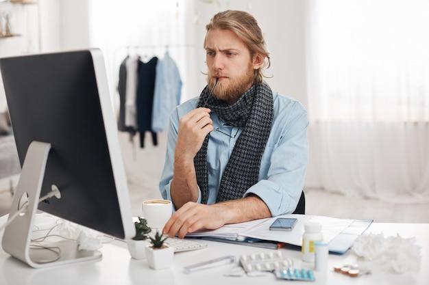 Uomo barbuto malato malato si siede davanti al computer, cerca di concentrarsi sul lavoro, tiene gli occhiali in mano. impiegato esausto stanco, ha uno stile di vita sedentario, isolato su sfondo ufficio.