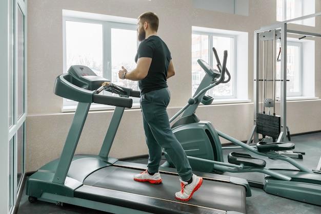 Uomo barbuto muscolare atletico che corre sui tapis roulant