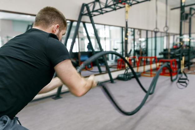 Uomo barbuto muscolare atletico che si esercita in palestra