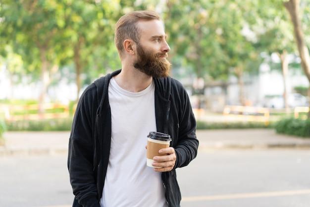 Uomo barbuto pensieroso che cammina in città e che tiene tazza di plastica