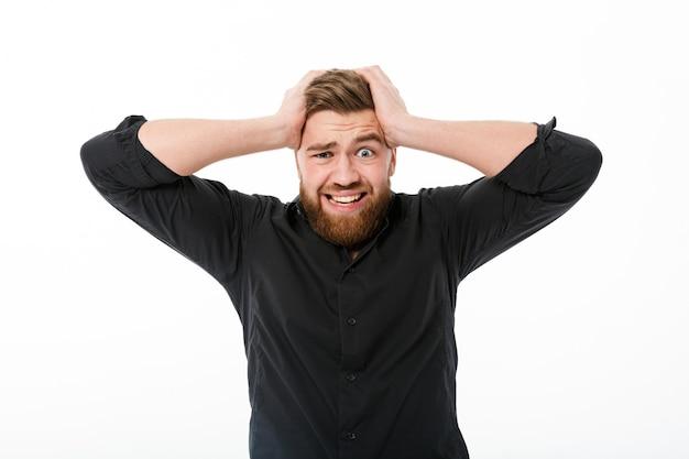 Uomo barbuto preoccupato in camicia che tiene la sua testa