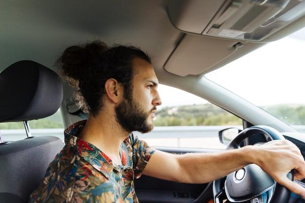Uomo barbuto serio che guida in macchina