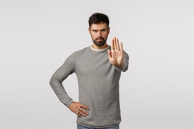 Uomo barbuto serio e assertivo che cerca di prevenire incidenti, limitare o avvisare, tirarsi indietro, allungare il braccio nel gesto di arresto, aggrottare le sopracciglia arrabbiato e fiducioso, vietare o vietare azioni