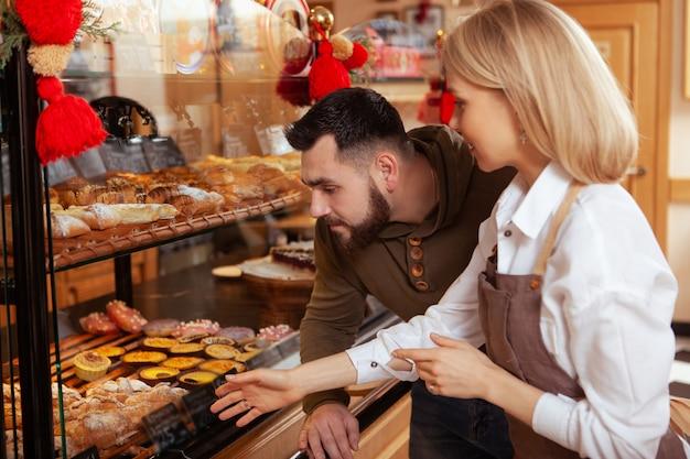 Uomo barbuto shopping al panificio locale, guardando la pasticceria sul display