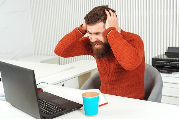 Uomo barbuto sollecitato che tiene la testa con la mano sul posto di lavoro. uomo che guarda il portatile. manager con problemi, cattive notizie. broker e indicatori finanziari. prezzi delle azioni in calo.