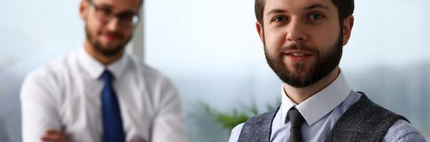 Uomo barbuto sorridente bello dell'impiegato nello sguardo del posto di lavoro a porte chiuse