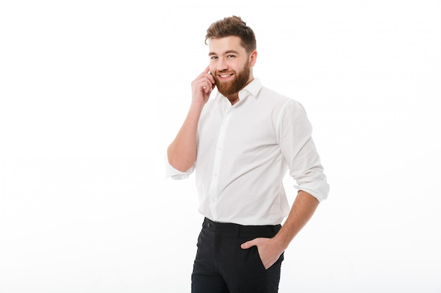 Uomo barbuto sorridente in vestiti di affari che parla dallo smartphone