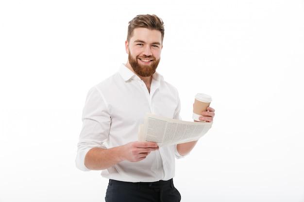 Uomo barbuto sorridente in vestiti di affari che tengono giornale