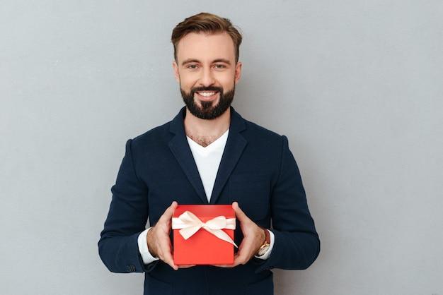 Uomo barbuto sorridente in vestiti di affari che tengono regalo