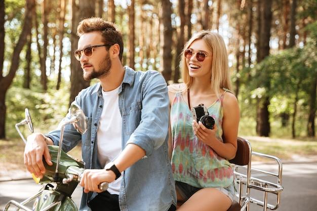 Uomo barbuto su scooter con la fidanzata all'aperto
