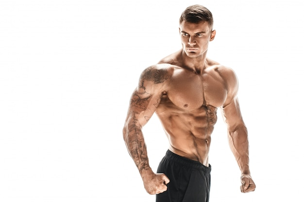 Uomo bello ad alto livello muscolare che posa sul backgroun bianco