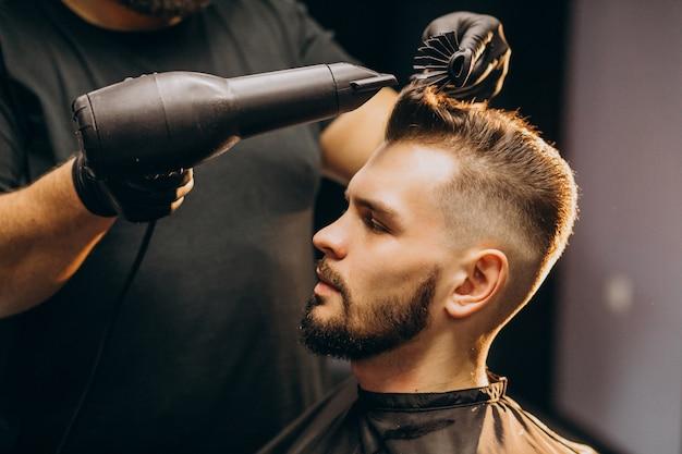 Uomo bello ad un negozio di barbiere che disegna capelli