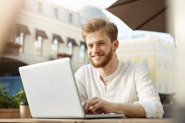 Uomo bello adulto dello zenzero con il computer portatile che si siede sul terrazzo di un ristorante o di un caffè