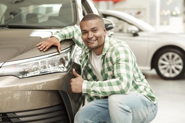 Uomo bello africano felice che mostra i pollici su che posano vicino alla sua nuova automobile al concessionario