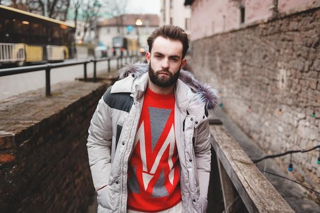 Uomo bello alla moda con una barba in una giacca invernale con pelliccia in posa all'aperto.