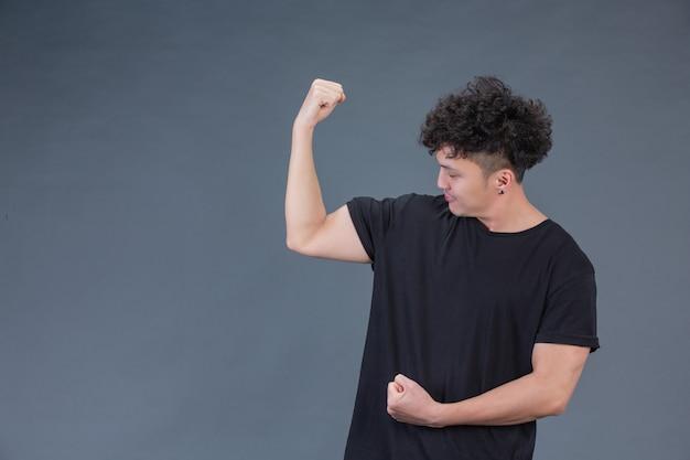 Uomo bello allo studio che mostra i muscoli delle braccia